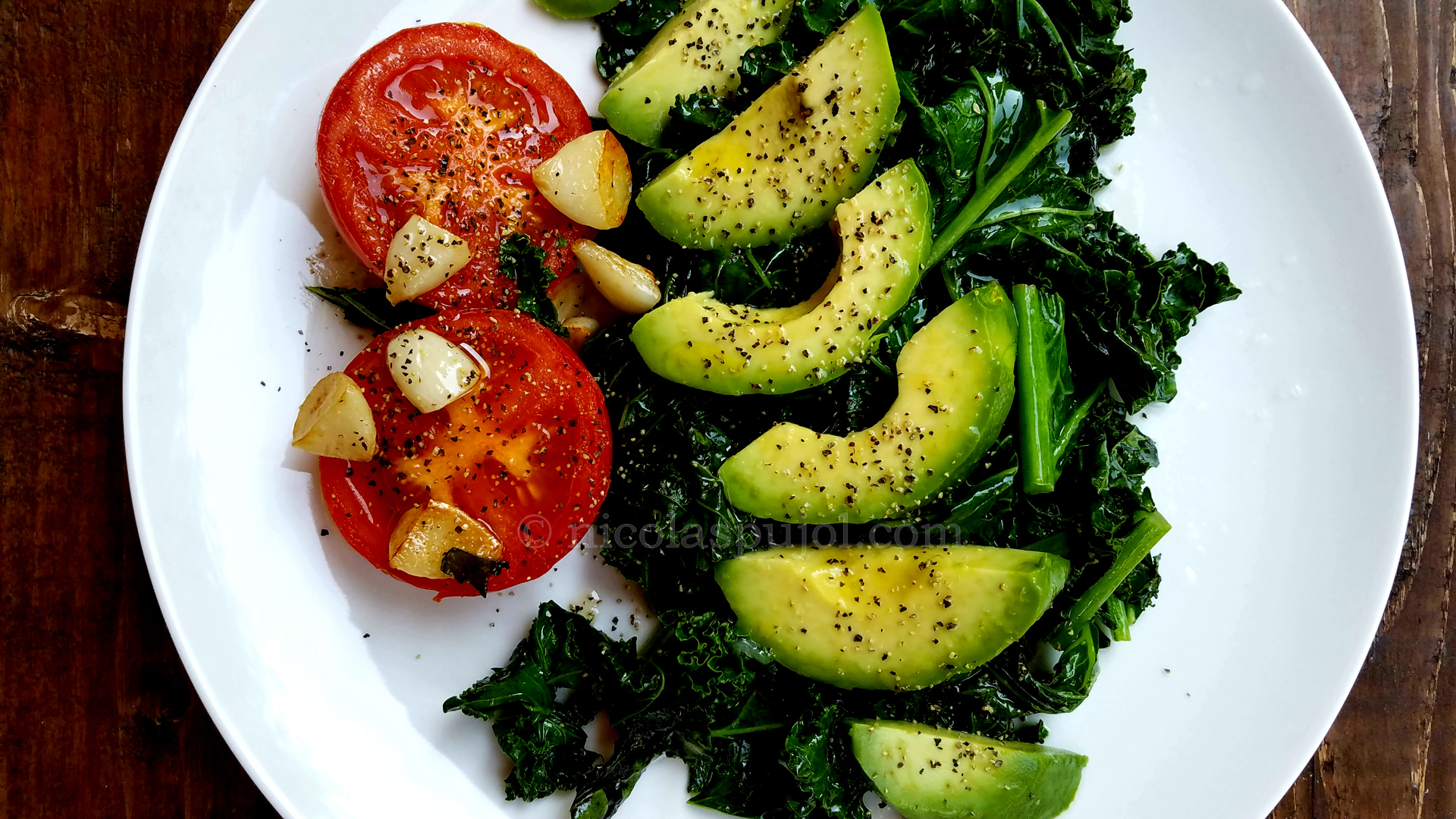Seared kale and tomato with avocado olive oil and lemon