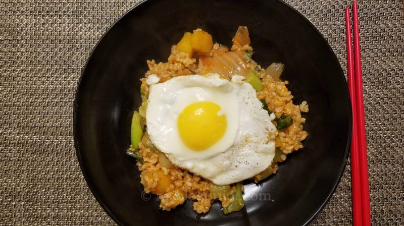 A plate of kimchi brown rice stir fry with an egg