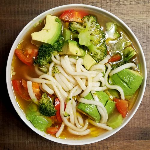 Udon noodle soup with avocados tomato, broccoli, olive oil