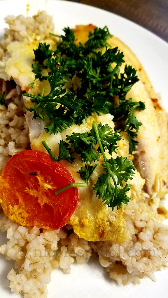 Presentation serving for oven baked tilapia in coconut milk, tomato and parsley