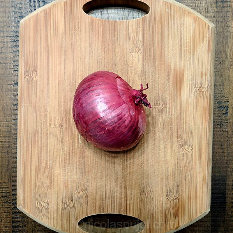 raw red onion on cutting board