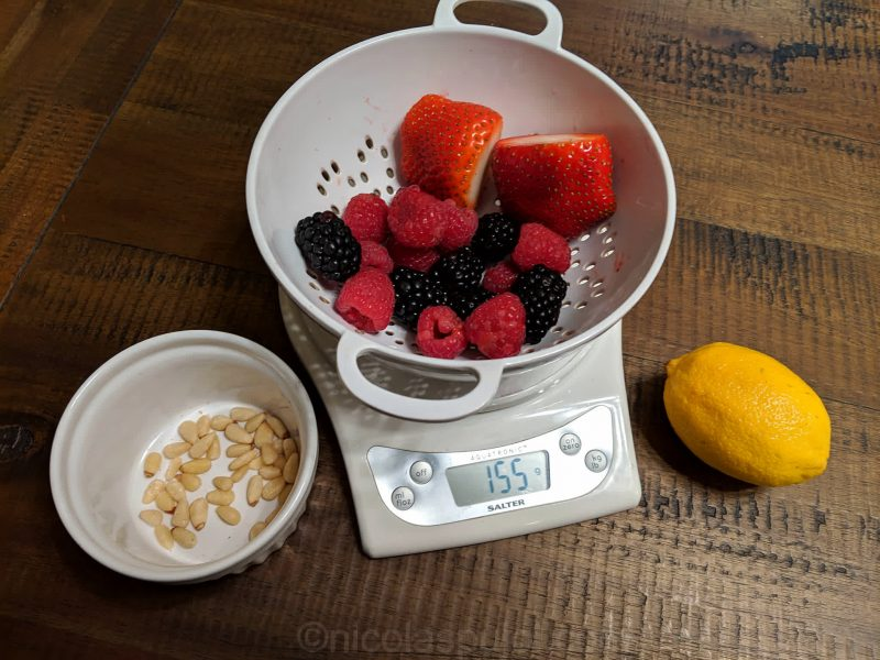 Weighing the mixed berries and nuts for caloric content