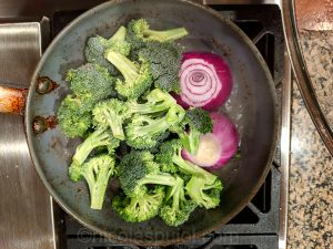broccoli and onion in frying pan