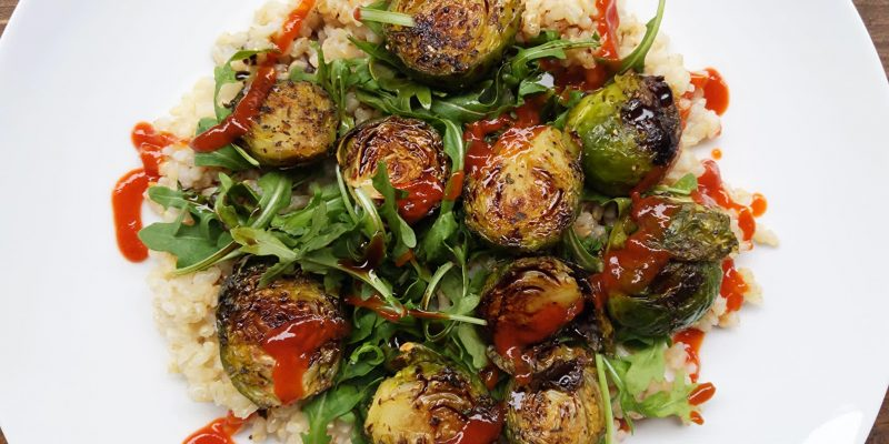 Baked Brussels sprouts on arugula, brown rice and balsamic vinegar