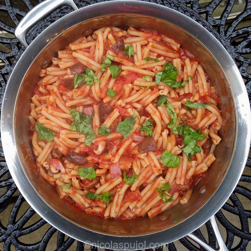 Large pan of vegan pasta in tomato sauce with basil