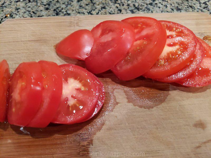 Slicing tomatoes for vegan caprese salad