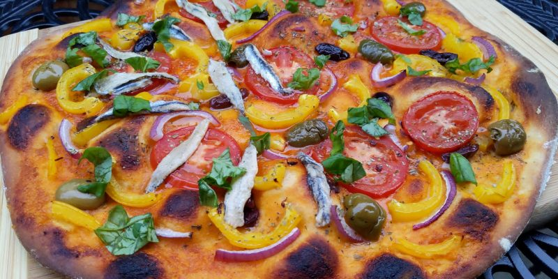 Spanish brava sauce pizza with vegetables and side of anchovies